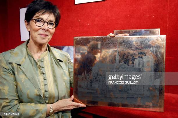 Auctioneer Patricia CasiniVitalis poses on June 15 in Paris with a photoengraving by Edouard Baldus depicting the NotreDamedeParis cathedral which...
