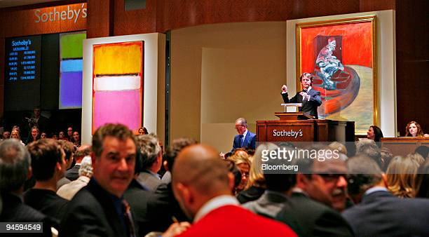 Auctioneer Tobias Meyer global head of contemporary art for Sotheby's acknowledges bids for Mark Rothko's painting 'White Center ' left during the...