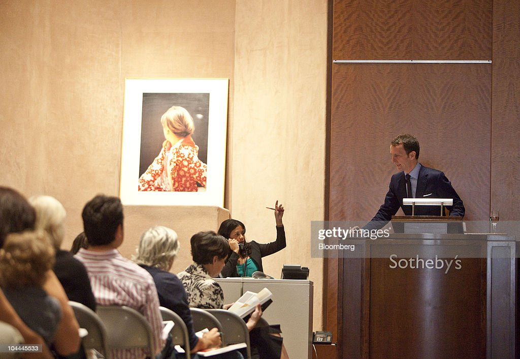 Auctioneer, Tobias Meyer, right, takes a phone bid for a photograph by Gerhard Richter titled 'Betty' as part of Lehman Brother's artwork collection at Sotheby's in New York, U.S., on Saturday, Sept. 25, 2010. Artworks being auctioned from the collection of Lehman Brothers Holdings Inc. may raise another $16 million for its creditors as collectors and souvenir hunters snap up remains of the collapsed bank. Photographer: Ramin Talaie/Bloomberg via Getty Images