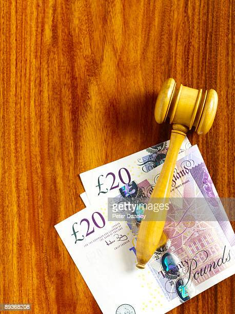 Auctioneer's gavel on sterling notes.