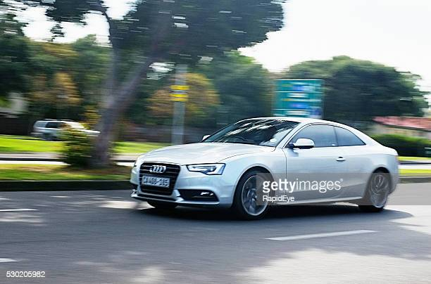 Audi A4 travelling on suburban main road.