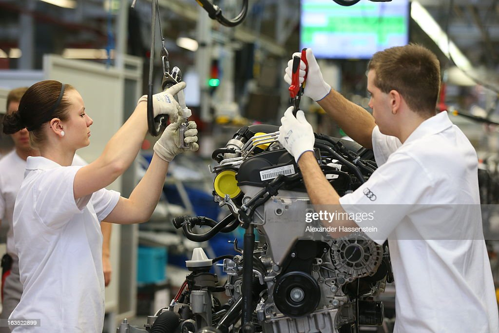 Audi employee work on an engine for an Audi A3 automobile, produced by Volkswagen AG's Audi brand, as the unit moves along the engine production line at the company's plant in Ingolstadt, Germany, on Monday, March 11, 2013. Audi is set to spend 13 billion euros ($17 billion) through 2016 to expand and develop new cars pursuing BMW?s sales lead.