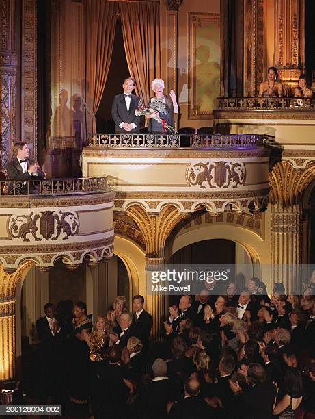 Audience applauding couple in balcony