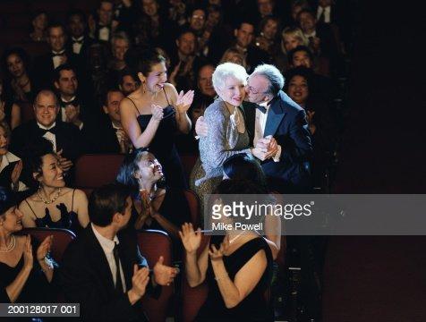 Audience applauding mature woman, husband kissing cheek : Photo