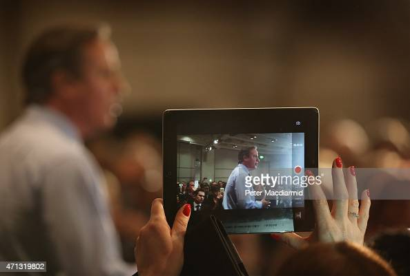 A audience member takes an iPad photo as Prime Minister David Cameron speaks to business leaders on April 27 2015 in London England Mr Cameron has...