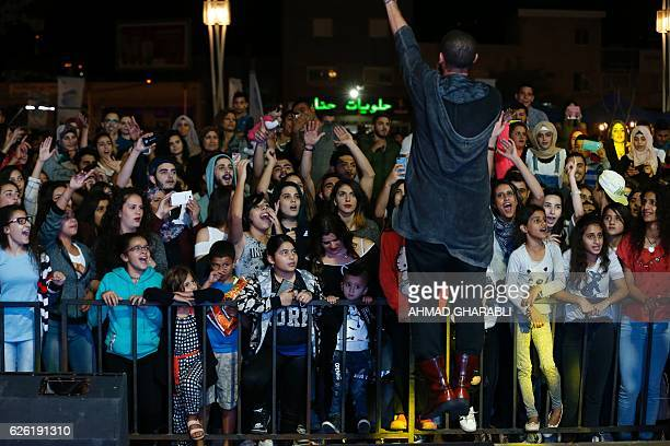 Audience members cheer as ArabIsraeli rapper Tamer Nafar performs onstage during a festival in the northern ArabIsraeli town of Sakhnin on October 23...