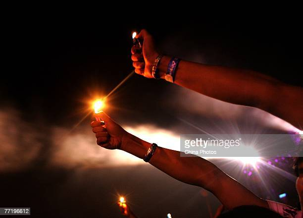 Audience members holds lighters during a performance of 2007 Snow Mountain Music Festival on October 4 2007 in Lijiang of Yunnan Province China The...