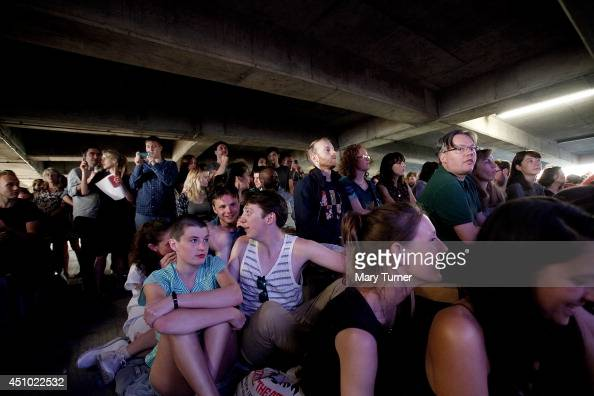 Audience members listen to The MultiStory Orchestra perform Jean Sibelius' 5th Symphony at the Peckham Rye Car Park on June 21 2014 in London England...