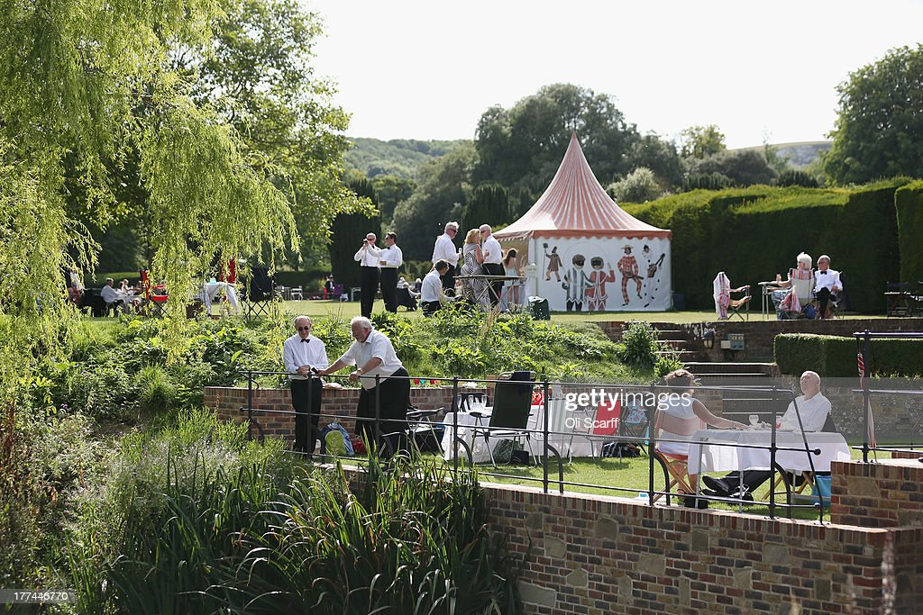 Audience members picnic in the grounds of Glyndebourne opera house before a production of the Benjamin Britten opera 'Billy Budd' on August 22, 21013 in Lewes, England. The Glyndebourne Festival of six operas performed at the East Sussex opera house from May until August sees its final performance of the season on August 25, 2013. The Glyndebourne opera house stands in the grounds of the country home of John Christie, who founded it in 1934, today it is recognised globally as one of the world's great opera houses.