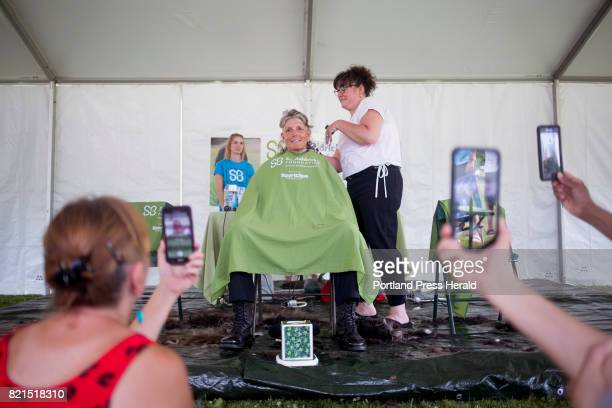 Audience members record video as Westbrook Chief of Police Janine Roberts has her head shaved to raise money for St Baldrick's Foundation a childhood...