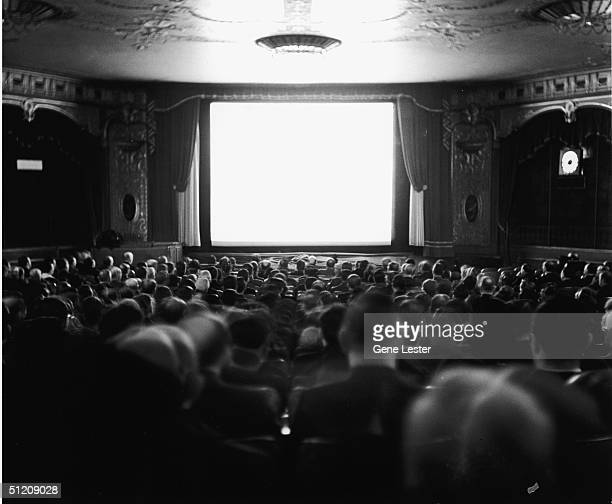 Audience members sit in their seats and watch the screen at the Newsreel Theatre on Broadway and 47th Street New York New York January 25 1940