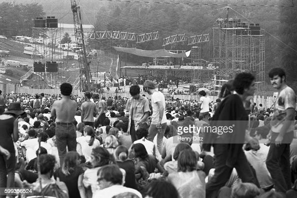 Audience members sit within distant view of the stage at the free Woodstock Music and Art Fair The festival took place on Max Yasgur's dairy farm...