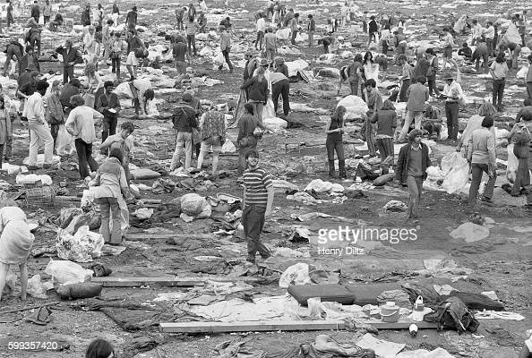 Audience members stand among piles of debris as they leave the free Woodstock Music and Art Fair The festival took place on Max Yasgur's dairy farm...
