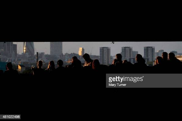 Audience members stand in front of the London skyline as they listen to The MultiStory Orchestra perform Jean Sibelius' 5th Symphony at the Peckham...