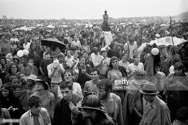 Audience members stand in the rain at the free Woodstock Music and Art Fair The festival took place on Max Yasgur's dairy farm which he rented to...