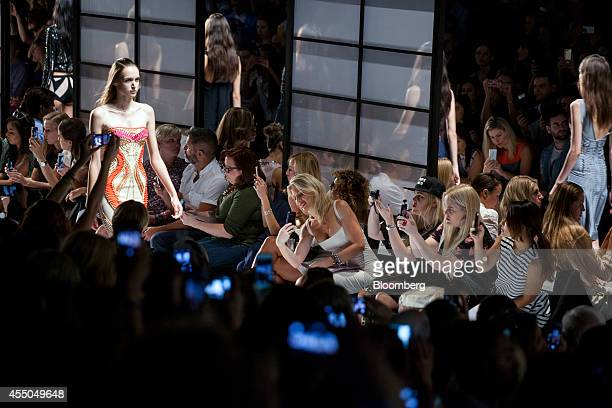 Audience members use smartphones and cameras to photograph the Herve Leger by Max Azria fashion show during MercedesBenz Fashion Week Spring 2015 at...