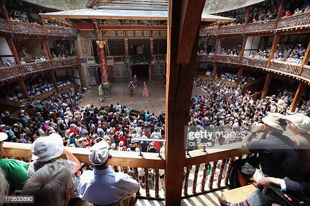 Audience members watch a production of 'A Midsummer Night's Dream' in Shakespeare's Globe theatre on the Southbank of the River Thames on July 16...