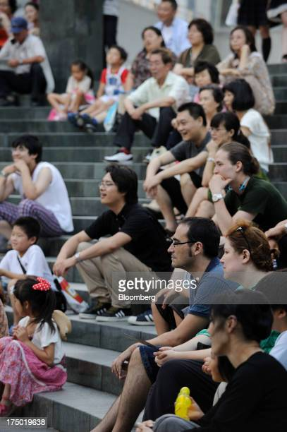 Audience members watch a street performance at an amphitheater in Yokohama Kanagawa Prefecture Japan on Saturday July 27 2013 Bank of Japan Governor...