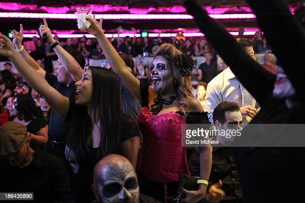Audience members watch the Lucha Vavoom Noche de los Salvajes Halloween show at the Mayan Theater on October 30 2013 in Los Angeles California Lucha...