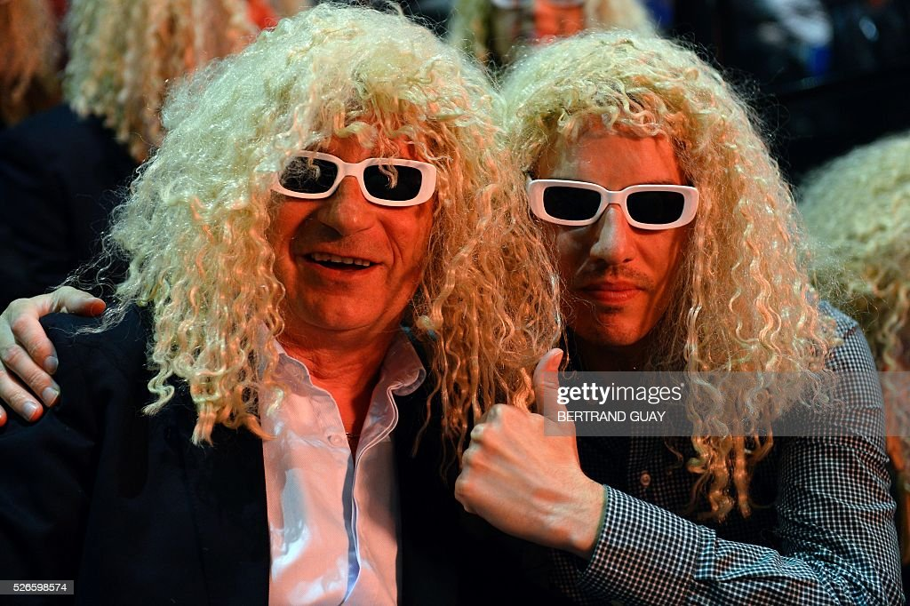 Audience members wearing sunglasses and wigs to dress up as French singer Michel Polnareff pose during a Polnareff concert in Epernay, eastern France, on April 30, 2016. / AFP / BERTRAND