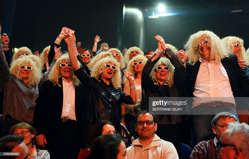 Audience members wearing sunglasses and wigs to dress up as French singer Michel Polnareff gesture during a Polnareff concert in Epernay, eastern France, on April 30, 2016. / AFP / BERTRAND