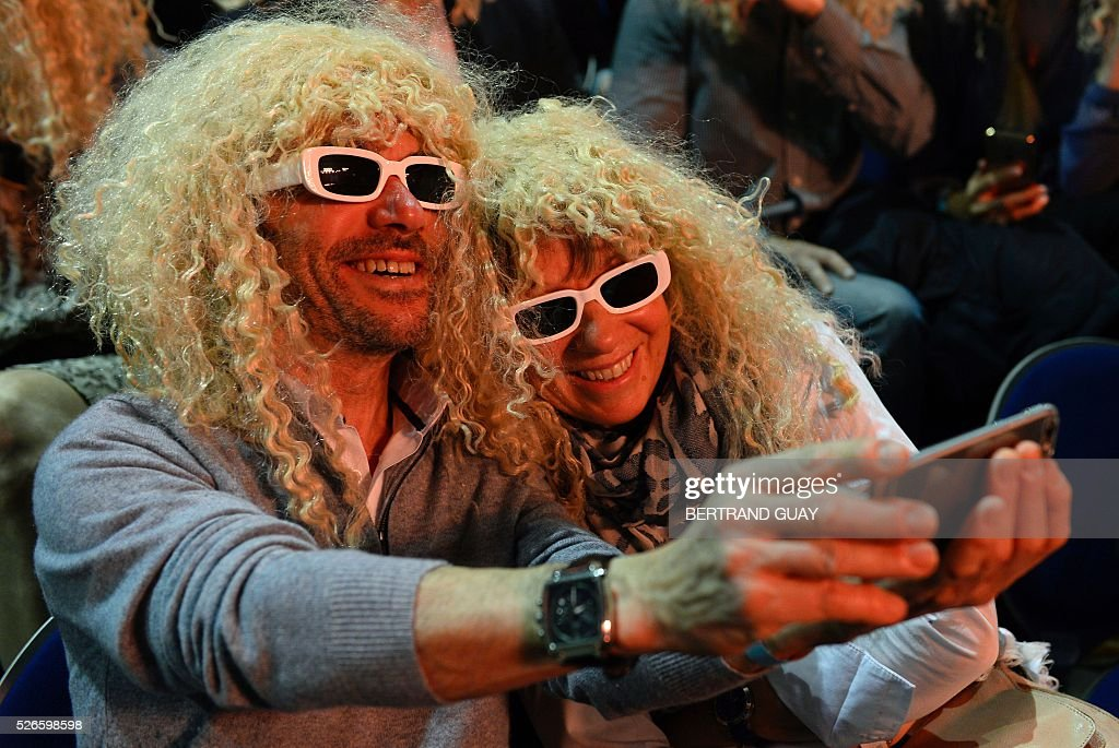 Audience members wearing sunglasses and wigs to dress up as French singer Michel Polnareff pose for a selfie photograph during a Polnareff concert in Epernay, eastern France, on April 30, 2016. / AFP / BERTRAND