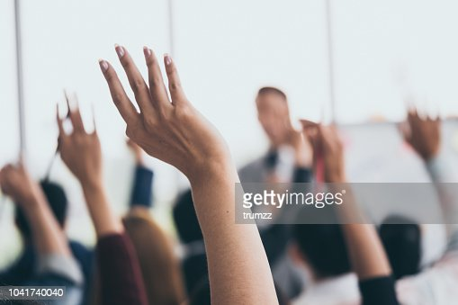 Audience raising hands up while businessman is speaking in training at the office. : Stock Photo