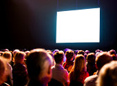 Crowd stares at a large screen in a dimly lit room.  The crowd is sitting in organized rows, and the screen is shining so brightly that it appears white.