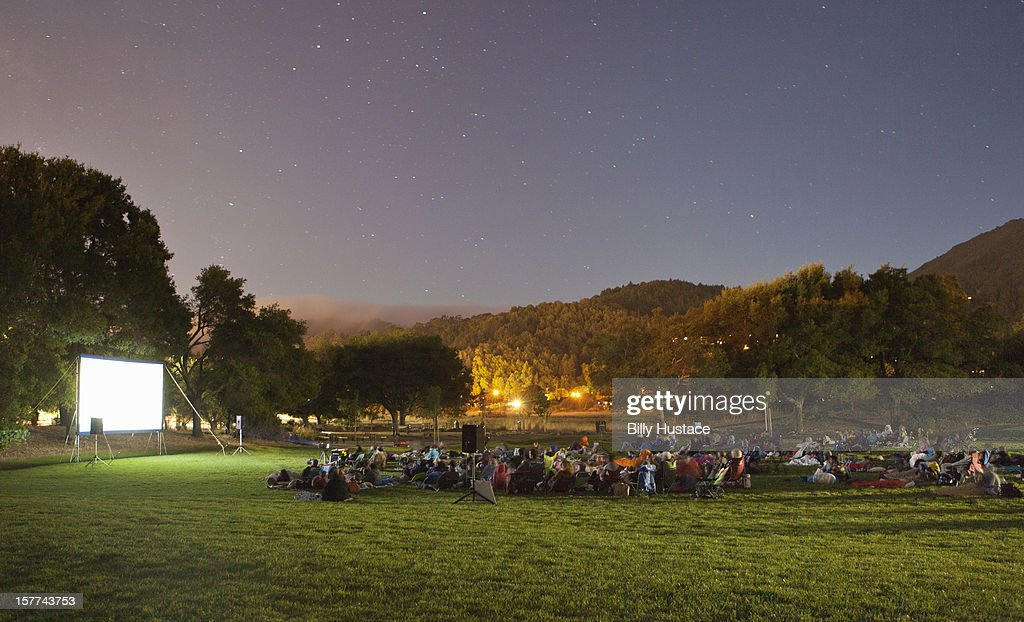 Audience watching a movie in a park at night. : Stock Photo