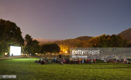 Audience watching a movie in a park at night.
