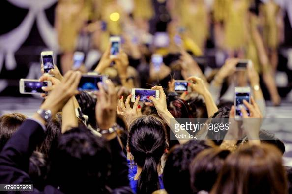Audiences take pictures with their phone during the DIANE von FURSTENBERG show as part of Mercedes Benz Fashion Week TOKYO 2014 A/W at Shibuya...