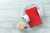 Audio book concept. Headphones, coffee and old book over wooden table. Top view with space for your text