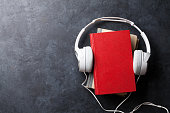 Audio book concept. Headphones and books over stone table. Top view with space for your text