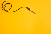 Audio jack with black cable isolated on yellow
