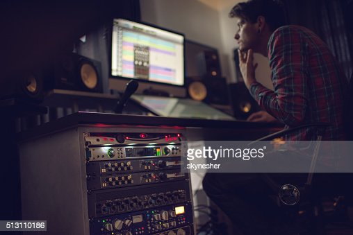 Audio rack in recording studio with producer in the background.