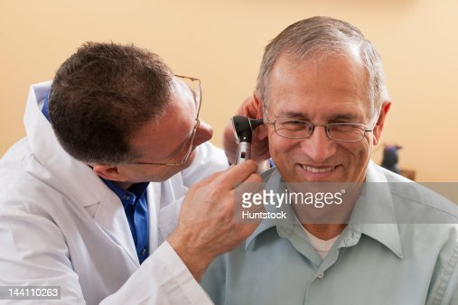 Audiologist doing an ear canal inspection : Stock Photo