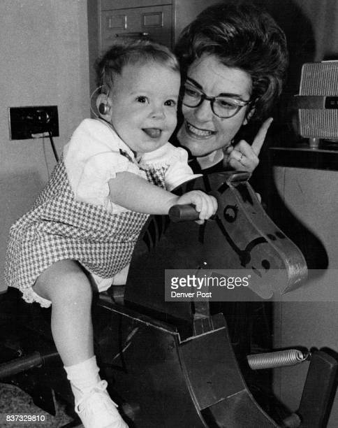 Audiologist Mrs Doreen Pollock loudly plays taped music 'with lots of rhythm' for Lisa's ride on a rocking horse Credit Denver Post