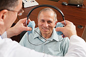 Audiologist placing a headset on patient for audiometric evaluation