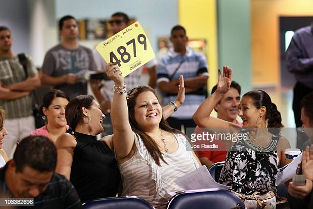 Audra Becera flashes her number as she gets the winning bid on a home during a Fannie Mae foreclosed home auction at the Miami Beach Convention...