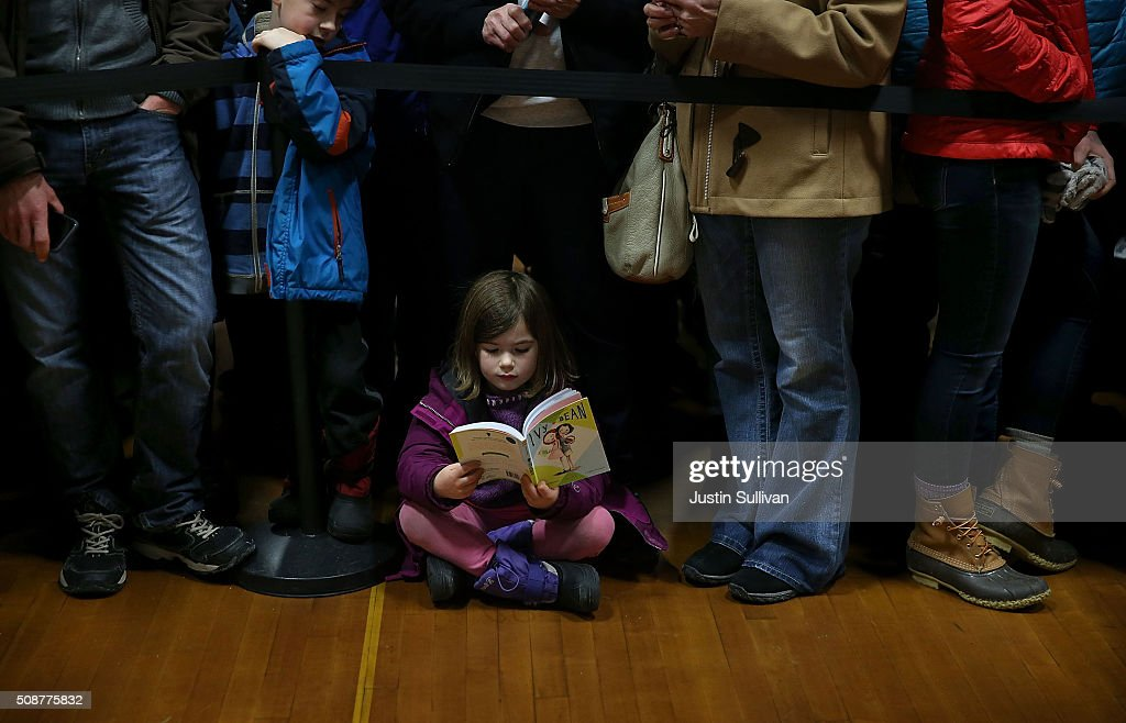 Audrey Clendenning reads a book as she waits for the arrival of democratic presidential candidate former Secretary of State Hillary Clinton during a get out the vote organizing event at Rundlett Middle School on February 6, 2016 in Concord, New Hampshire. With less than one week to go before the New Hampshire primaries, Hillary Clinton continues to campaign throughout the state.