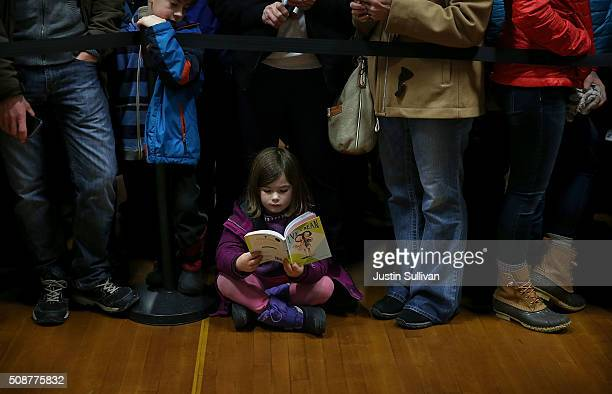 Audrey Clendenning reads a book as she waits for the arrival of democratic presidential candidate former Secretary of State Hillary Clinton during a...