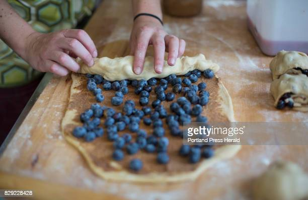 Audrey Farber rolls up her dough while blueberry and cinnamon rolls at Fork Food Lab