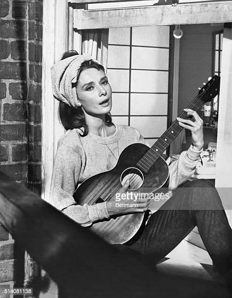 Audrey Hepburn playing guitar