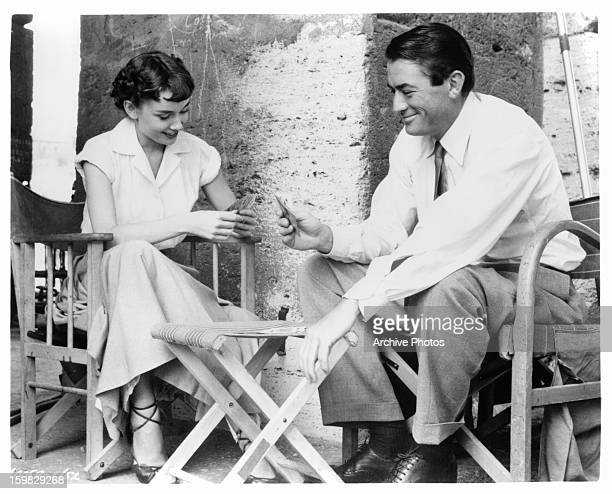Audrey Hepburn plays cards with Gregory Peck in a scene from the film 'Roman Holiday' 1953