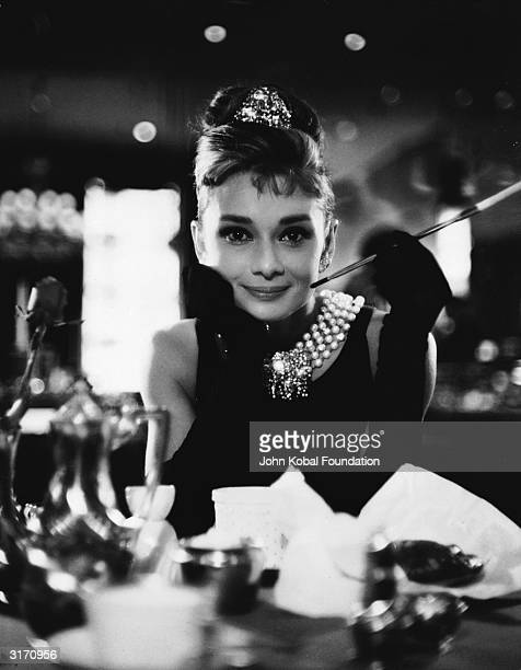 Audrey Hepburn wields a cigarette holder in her role as the charming golddigger Holly Golightly in 'Breakfast at Tiffany's' directed by Blake Edwards