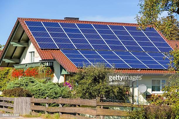 Auf einem Einfamilienhaus werden Solarzellen für alternative Sonnenenergie verwendet