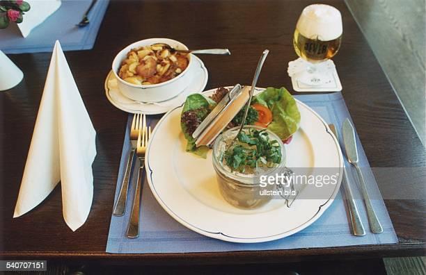 Auf einem mit drapierter Stoffserviette Set und Besteck gedeckten Restauranttisch ein geöffnetes Weckglas mit Sauerfleisch in Aspik serviert auf...