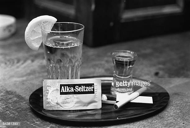 ein Wasserglas mit einer Zitronenscheibe 'AlkaSeltzer' eine Zigarette auf einer geöffneten Streichholzschachtel und ein Glas mit klarem Schnaps