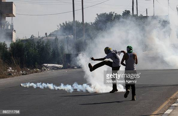 NABLUS Aug 18 2016 A Palestinian protester throws back a tear gas canister towards Israeli troops during clashes following a protest in solidarity...