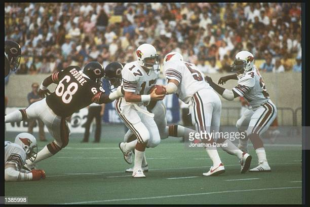 St Louis Cardinals quarterback Jim Hart avoids the grasp of a Chicago Bears defensive lineman during a preseason game at Soldier Field in Chicago...